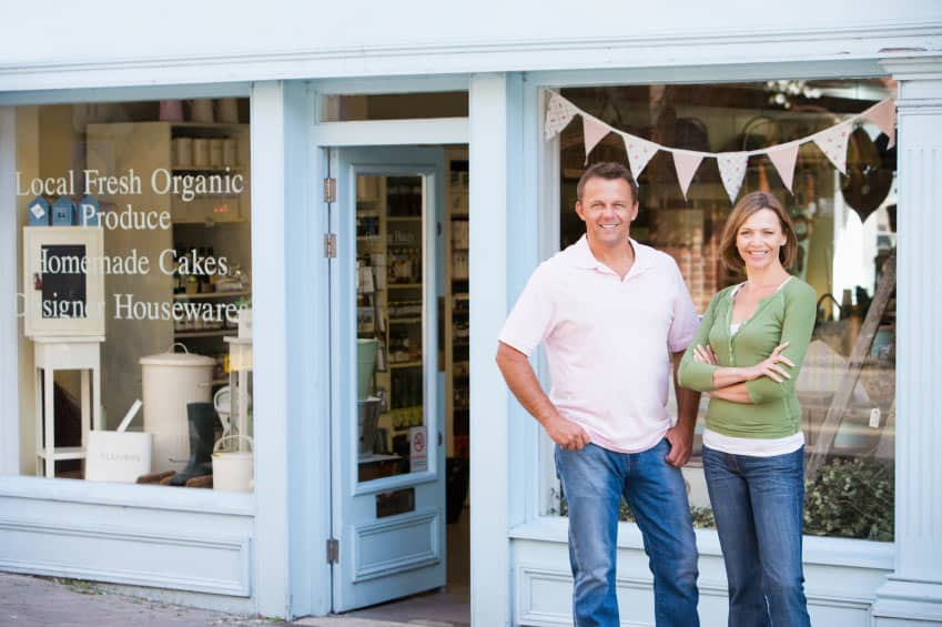 Two store owners outside their shop that is protected by grocery store insurance